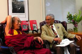 Clay Carson and the Dalai Lama sit in leather chairs next to each other. They are smiling, and the Dalai Lama's right arm is raised and bent backwards, touching the top of his chair.