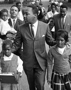 King escorts children to their newly integrated school, 20 September 1965. King has hands on the shoulders of two black girls as they walk.