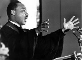 King preaches to the congregation of Ebenezer Baptist Church with arms stretched wide, 30 April 1967
