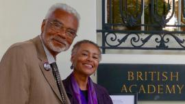 "Dr. Carson with filmmaker Judy Richardson at British Academy conference on Civil Rights Documentary Cinema and the 1960s. Richardson stands to Dr. Carson's left. They are standing in front of a plaque that reads ""British Academy."" Both are smiling."