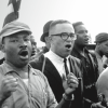 Martin Luther King and John Lewis lead singing marchers toward Montgomery. King has both arms raised with his fists clenched.